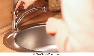 Washing tomato - Young woman washing tomato.