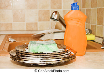 Washing-up liquid with a sponge on kitchen
