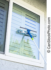 Washing window on a home - Window washer uses a sponge and...