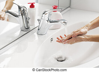 Washing - Woman washing hands in bathroom close up