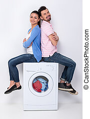 Washing - Young beautiful couple are sitting on the washing ...