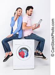 Washing - Young beautiful couple are using laptop and...