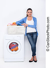 Washing - Young housewife is doing laundry with washing...