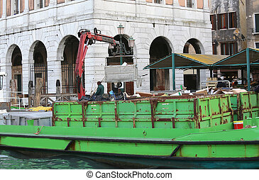 waste collection boat and an ancient palace in the background