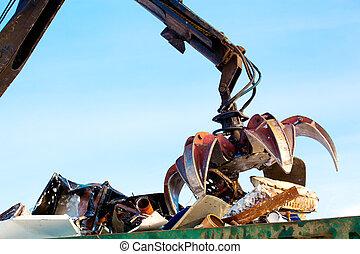 Machine loader with hydraulic multivalve crab bucket uploads waste steel into a truck