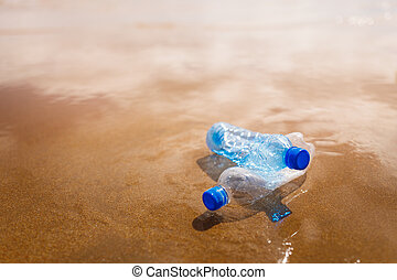 wasted plastic bottles on beach