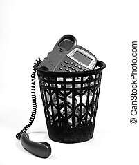 vertical image of full wastepaper with crumpled papers and old-fashion phone on white background