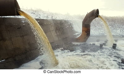 Wastewater from two large rusty pipes merge into the river...