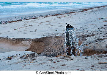 water from sewer pipe, wastewater on the seashore