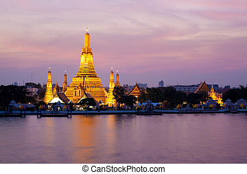 Wat Arun glowing in the pink twilight by Chao Phraya River, Bangkok, Thailand
