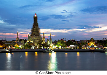Wat Arun Rajwararam temple and light trail from the boat at night in Thailand.