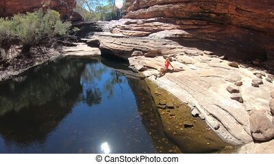 Permanent waterhole in Garden of Eden reflecting sandstone walls of Kings Canyon, Watarrka National Park. Woman enjoys natural pool.Trekking in Australia Outback Red Center Northern Territory