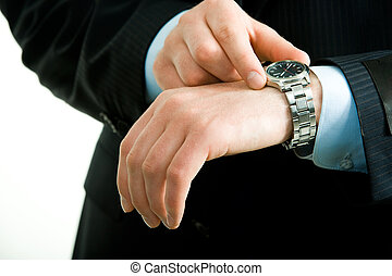Closeup of businessman�s hand with watch on it while he checking the time