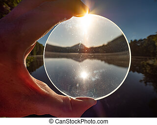 . Glass orb on o by the lake in a beautiful sunrise