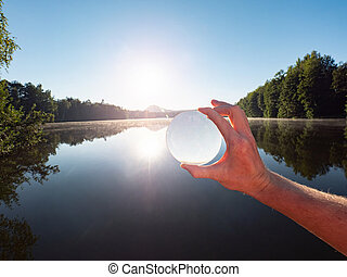 Watch the lake and sunset through glass lens or sphere.