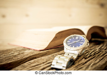 Watch with open book on old wooden table, vintage style.