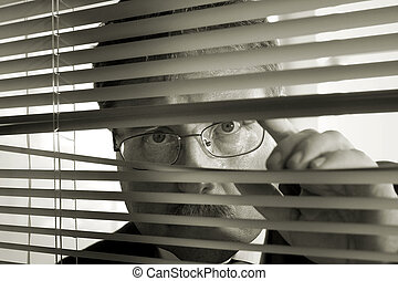 Watchful Eye - a businessman peers through the blinds