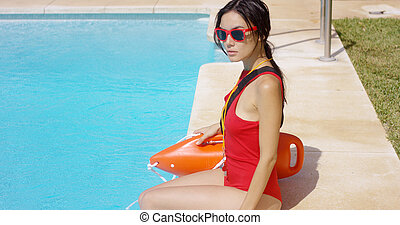 Watchful lifeguard sitting at side of pool - Watchful female...