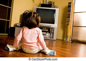 Watching cartoons - Rear view of little girl sitting on the ...