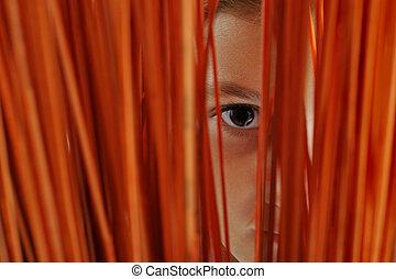 Close up of a girls eye wacthig through a slit