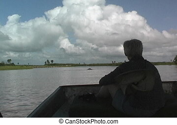 Hippo comes out of the water in front of the boat on the Rufiji River