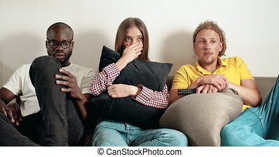 Watching Horror Film - Mixed race group of young frighntened...