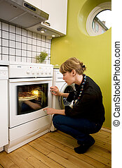 Watching a homemade Italia style pizza bake in the oven in an apartment kitchen;