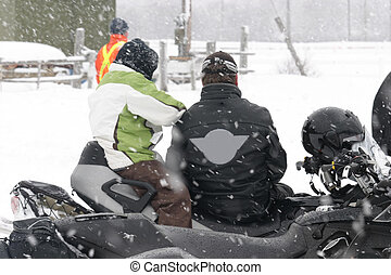 watching races - this couple sitting on snowmobile watching...