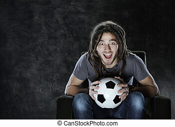 Watching soccer on tv - Young adult man exults watching...