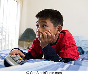 Watching television - Young asian boy laying down on his...