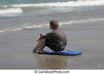 Watching The Tide - A boy sitting on his boogie board...