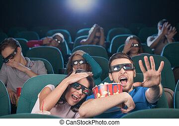 Watching three-dimensional movie. Terrified people in three-...