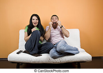 Watching TV a horror movie - Young man and woman ,friends...