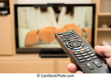 Watching TV and using black modern remote controller. Hand holding TV remote control with a television in the background. Shallow dof.