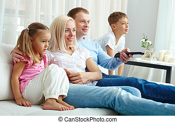 Watching TV - Happy family of four watching TV together on...
