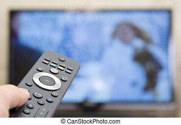 Watching TV. Remote control with blured tv on background