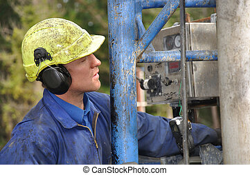 watching, watching - Drilling crewman studies cable as it...