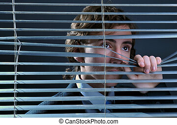 Young businessman looking through window blinds