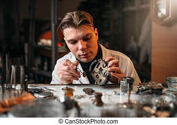 Watchmaker repair old mechanical clocks. Clock maker at work