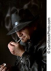 Mafia watchman lighting a cigarette in the dark