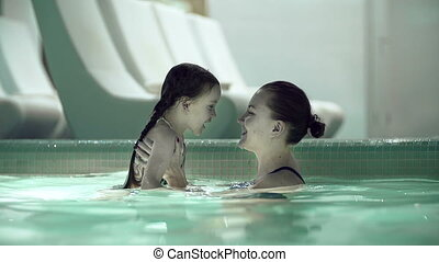 Water Activities - Mother holding and kissing her daughter...