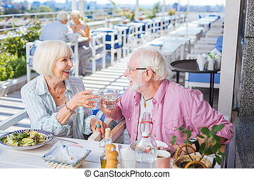 Happy aged couple holding glasses of water