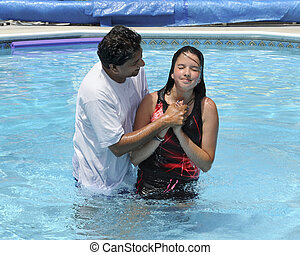 An Asian Indian pastor baptising a preteen in a swimming pool.