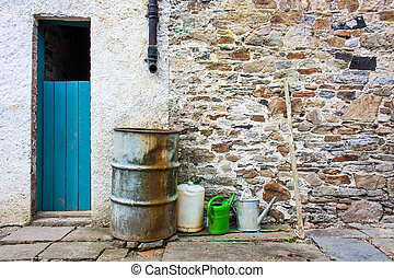 Water barrel and watering cans in backyard