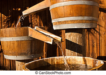 Wooden water barrels funnel water through chutes