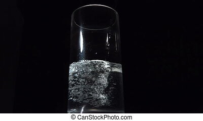 Water being poured in a glass in slow motion