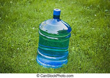 water big bottle on green grass background