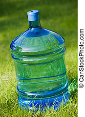 water big bottle on green lawn background