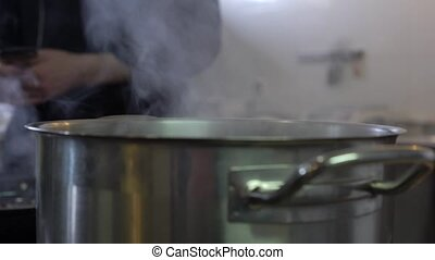 Water boils in an aluminum saucepan on an electric stove in a restaurant.