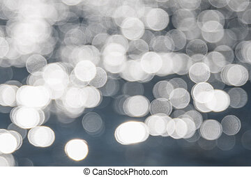 Water bokeh background. Defocused water surface with waves glittering in the sun